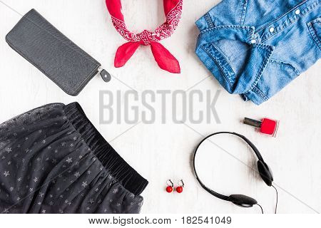 Top view of yong woman clothes and accessories. Tulle skirt denim shirt wallet head phones earrings nail polish and kerchief. Urban style concept.