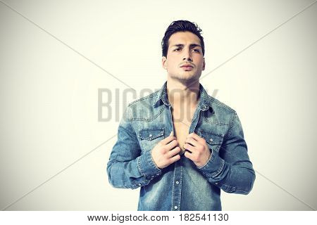 Confident, attractive young man with open denim shirt on muscular torso, ripped abs and pecs. Studio shot on neutral background