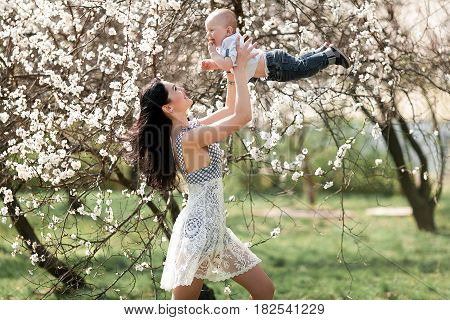 Young mother playing with her baby on walk in blooming garden. She tosses up baby and they laugh joyful.