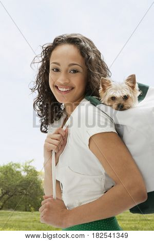 Mixed race teenage girl carrying dog on back