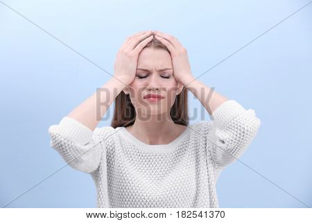 Beautiful young woman suffering from headache on color background