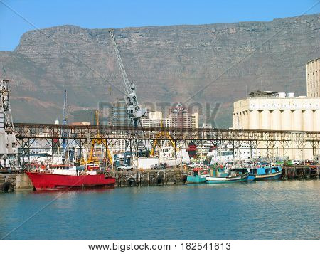 CAPE TOWN, SOUTH AFRICA, WITH BOATS AND BUILDINGS IN THE FORE GROUND AND PART OF TABLE MOUNTAIN IN THE BACK GROUND 12a