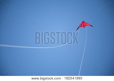 Blue sky, and flying red kite and white strings