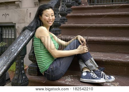 Asian woman sitting on front steps