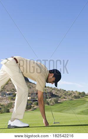 Hispanic man playing golf