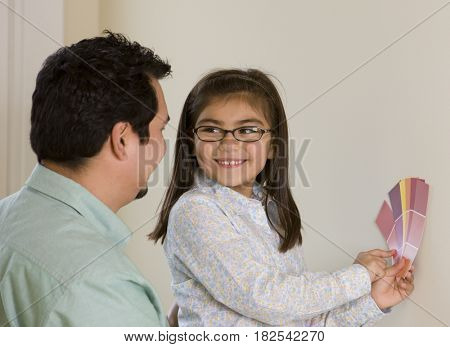 Hispanic girl with father choosing paint colors