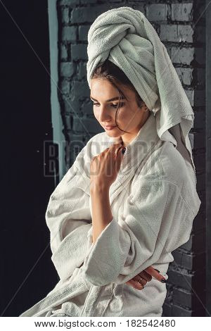 sexy young girl with dark hair, big eyes and dark eyebrows wearing white bath robe whith towel on her head. Model with light nude make-up, black studio background, beauty photo, copy space