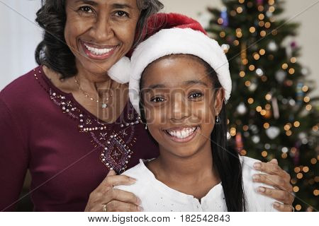 African woman with granddaughter in santa hat