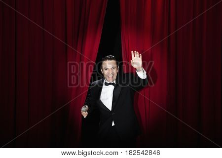 Hispanic man in tuxedo emerging from red curtains and waving