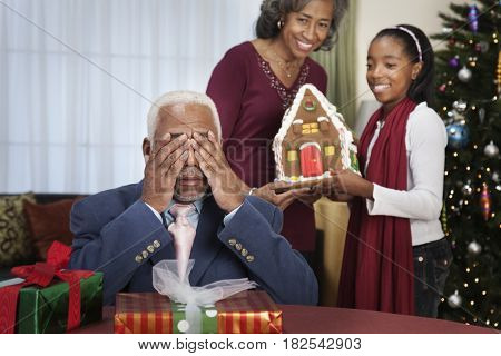 African man being surprised with gingerbread house
