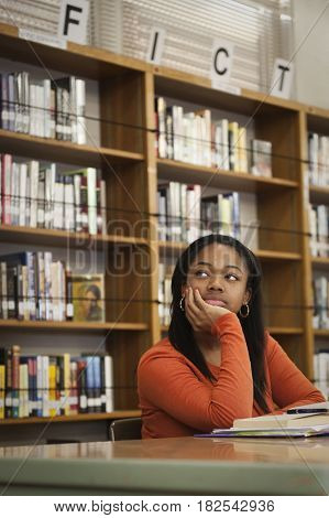 African teenage girl daydreaming in school library