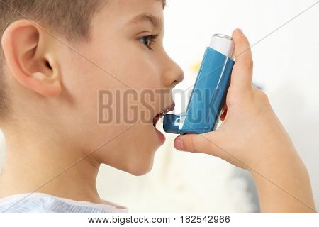 Little boy using asthma inhaler, closeup