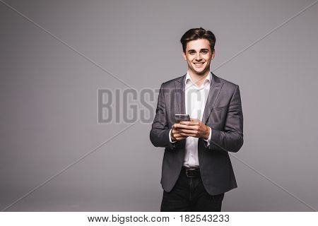 Portrait Of Young Business Man Texting A Message With Phone Over Gray Background