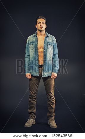 Confident, attractive young man with open denim shirt on muscular torso, ripped abs and pecs. Studio shot on neutral dark background