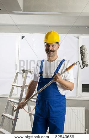 Manual worker wearing bib overalls holding paint roller.