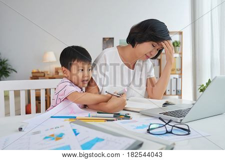 Little boy interfering with work of his mother