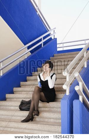 Hispanic businesswoman talking on cell phone outdoors