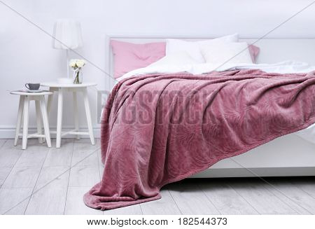 Comfortable bed with soft pink coverlet and pillows in light modern room