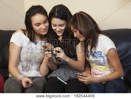 Teenage girls looking at digital camera