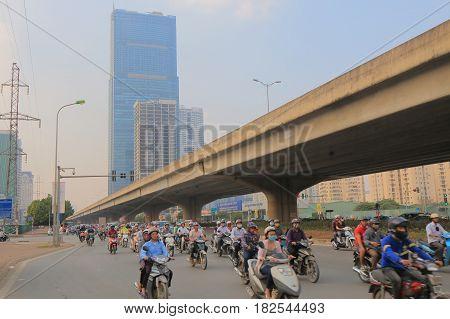 HANOI VIETNAM - NOVEMBER 23, 2016: Unidentified people drive motorbikes in Hanoi business district.