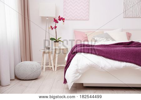 Comfortable bed with soft lilac coverlet and pillows in light modern room