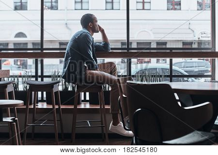 Enjoying nice day. Thoughtful young man looking outside while sitting in the cafeteria