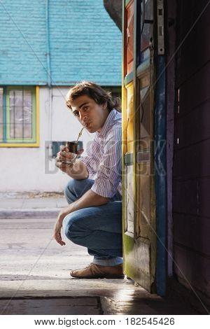 Hispanic man drinking and squatting in doorway