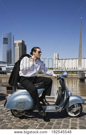 Hispanic businessman sitting on scooter