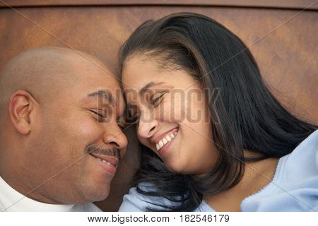 Dominican man lounging in bed with wife