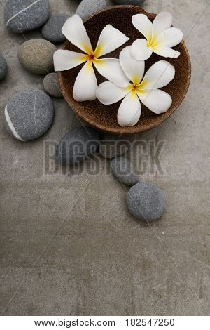 frangipani in wooden bowl with spa stones on grey background