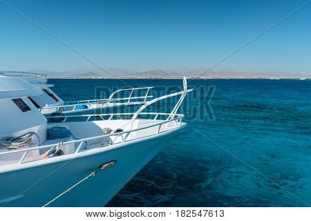 View at the coral sea and white yacht. Perfect place for snorkeling. Summer vacation at Red sea with turquoise clear water.