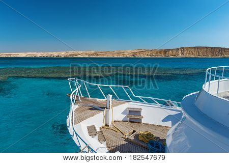 View at the coral sea and white yacht. Perfect place for snorkeling. Summer vacation at sea with turquoise clear water. Red sea with clear turquoise water.