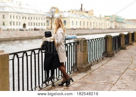 Blonde hair mother and her daughter are standing by the bridge which separates them from the river. Apparently, it's Saint Petersburg and the river is Neva. They are wearing warm clothes and showing to observers their backs