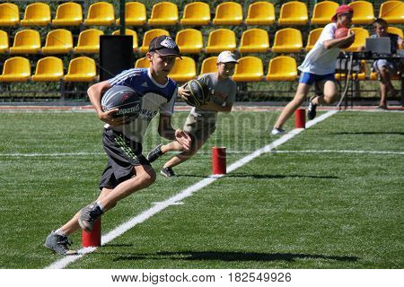 SVIATOHIRSK UKRAINE - JULY 30 2012: Unidentified boy runs with ball during the relay race in the children's recreation center