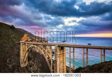 Scenic panoramic view of historic Bixby Creek Bridge along world famous Highway 1 in beautiful evening twilight with dramatic cloudscape during blue hour at dusk Monterey County California USA