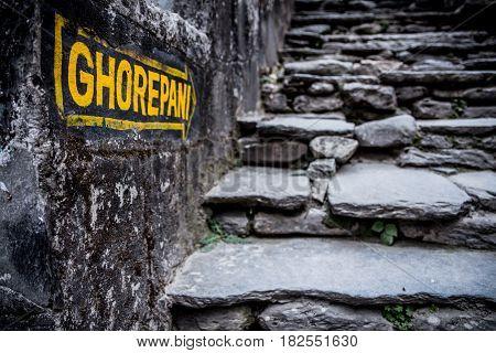 Nepal March 2017: A sign indicates the way to Ghorepani at Birethanthi the start of the Annapurna circuit trek in the Annapurna region Nepal.