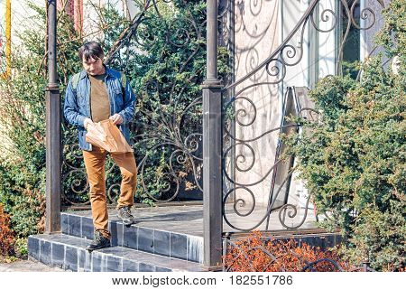 gloomy elderly man putting bread in a paper bag on the porch of the store on sunny spring day