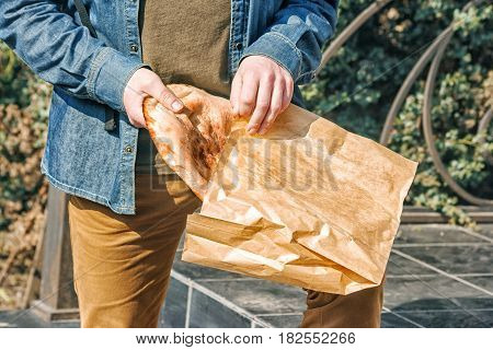 elderly man putting bread in a paper bag on the porch of the store on sunny spring day hands closeup