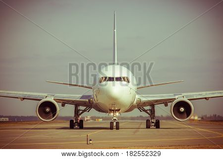 Jet passenger plane taxiing along the runway for takeoff - toned image