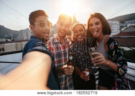 Group of people having a party on the rooftop making a selfie. Happy young friends taking self portrait during party.