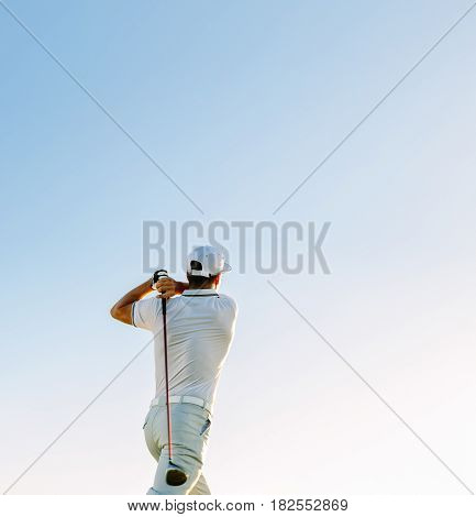 Man Swinging Golf Club Against Clear Sky