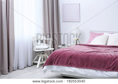 Comfortable bed with soft pink coverlet, pillows and chair in light modern room