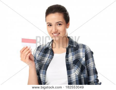 Beautiful young woman with business card on white background