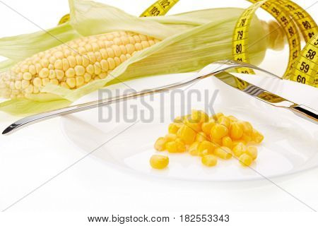 Fresh ripe ear of corn, plate with boiled corn kernels  and measuring tape on a white background. Healthy nutrition concept.