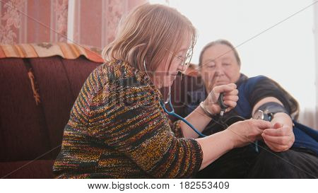 Two pensioners - senior ladies checking healthcare state with manometer - measures pressure, elderly lifestyle, close up