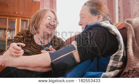 Two pensioners - senior ladies have fun - checking health state with manometer - measures pressure, pensioners healthcare, close up