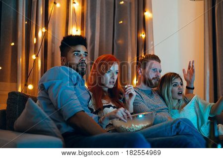 Shot of four scared friends watching a movie at home.