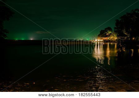 Green lighting from squip fishing boat with lighting resort in the dark sea at night of koh kood,Trat, Thailand