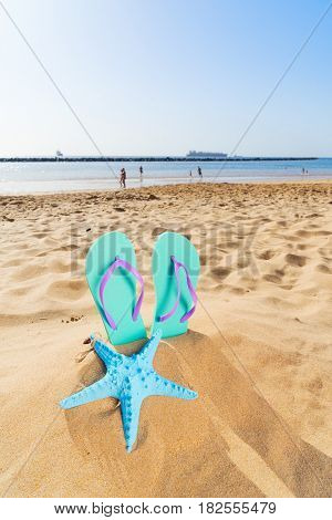 Summer beach fun - summer flip-flop sandals with starfish in beach sand