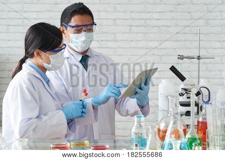 Microbiologists analyzing test results on digital tablet